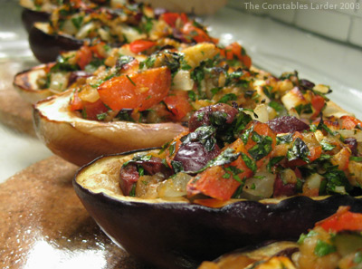 A row of roasted eggplant stuffed with vegetables and herbs.
