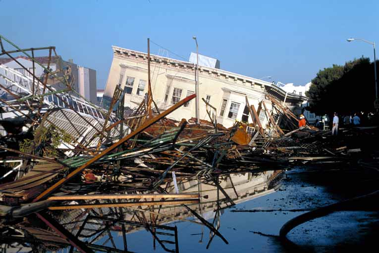 white building tilted and falling in front of crushed boats and water