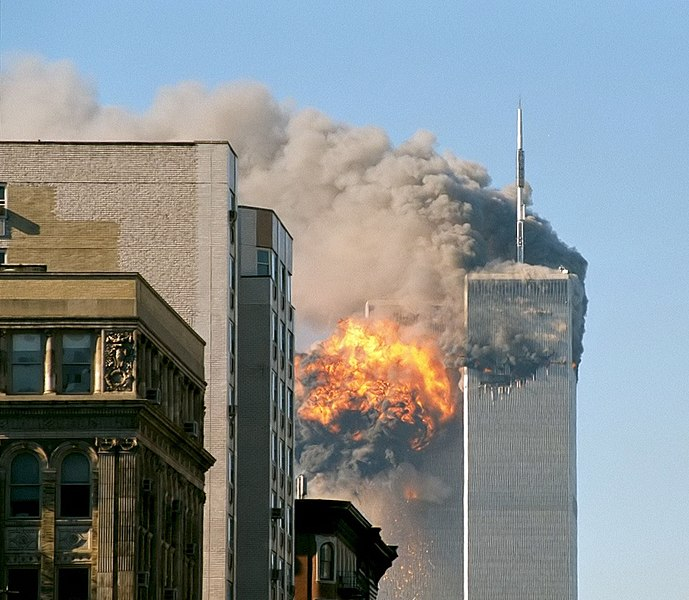 smoke and flames billow from the top of of the two tall rectangular World Trade Center towers