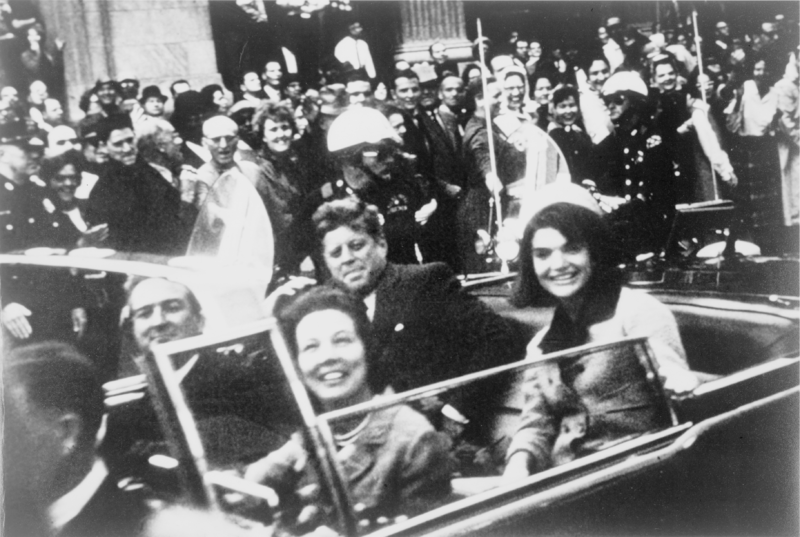 John F. Kennedy in a suit rides in the backseat of a convertible car with his wife Jackie in hat, smiling.