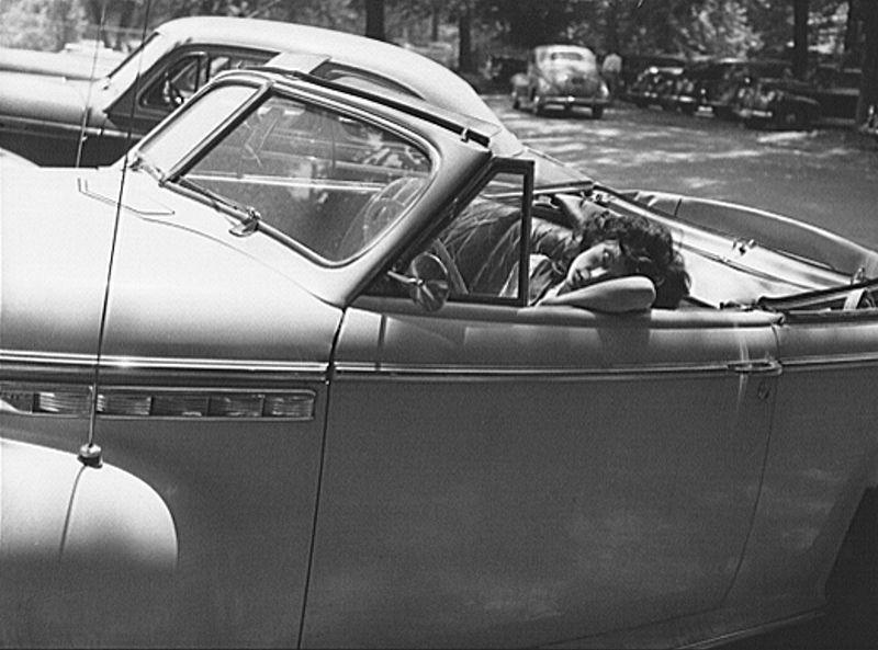 Young woman sleeps in the driver's seat of an old convertible.