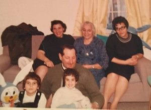Family photo of 6 people arranged on a couch for the camera