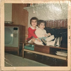 Two little girls sit almost on top of one another on a coffee table in from of the fireplace