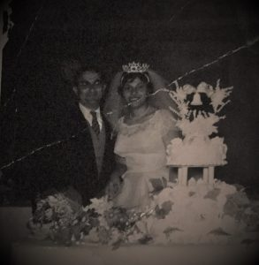 Husband and wife post next to 2-tier wedding cake.