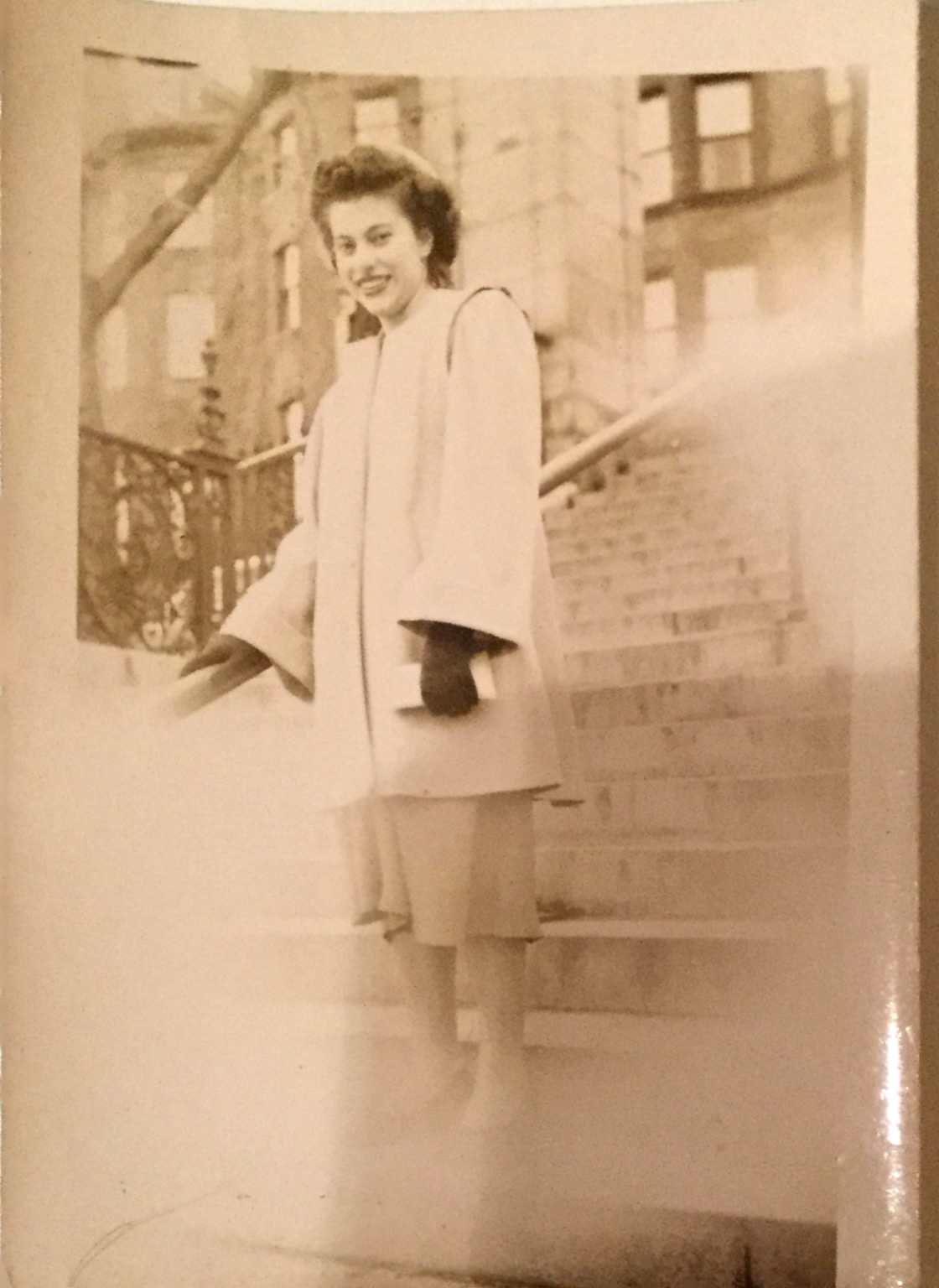 Smiling young woman dressed in a warm, formal coat and shoes standing on the steps.