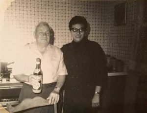 Older man holding a bottle standing next to woman in glasses.
