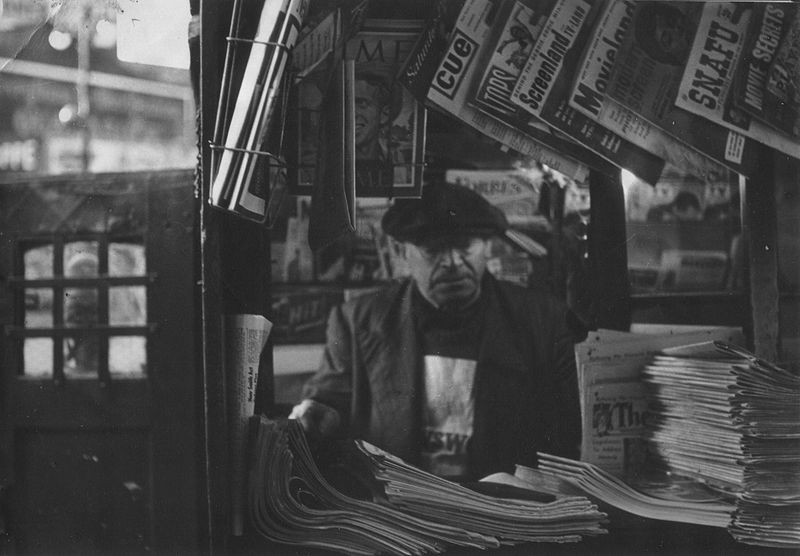 Middle-aged man sits behind the desk at a newsstand ready to sell the newspapers hanging all around him.