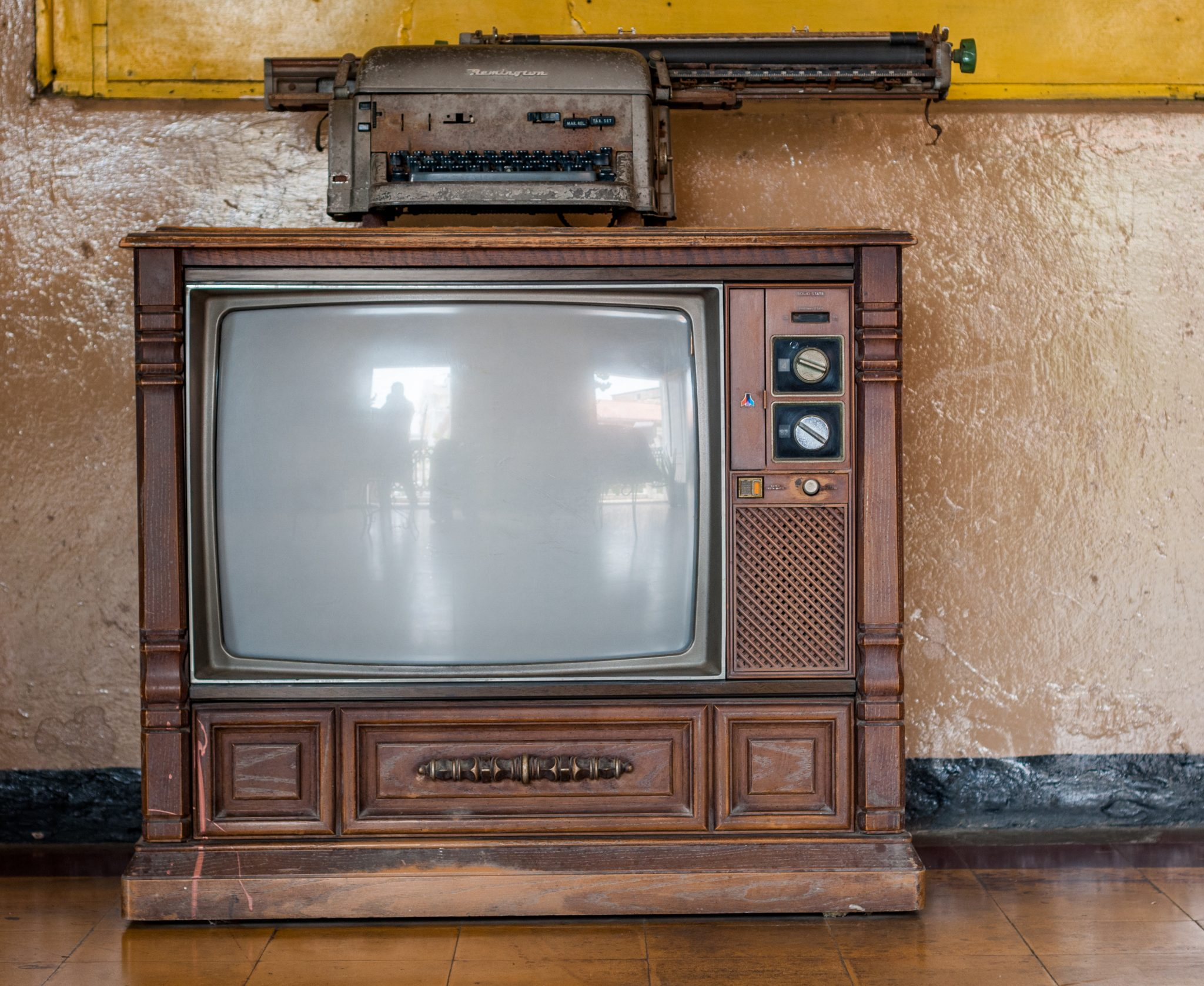 An old-style brown television in front of a tan wall