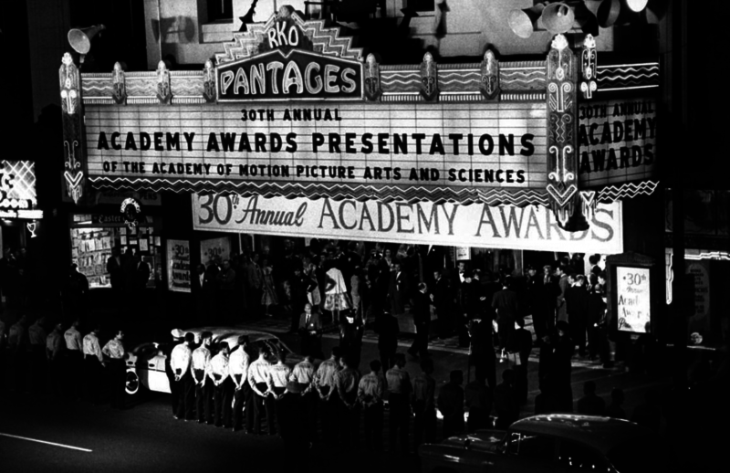 A crowd gatherings in front of a theater advertising the 30th Annual Academy Awards.