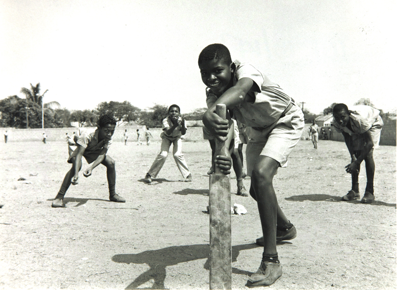 4 young school boys are arranged behind a cricket batter in Kingston, Jamaica.