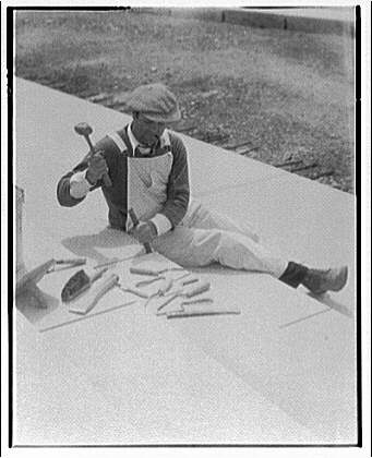Stonemason wielding chisel and hammer on the steps of a bridge.