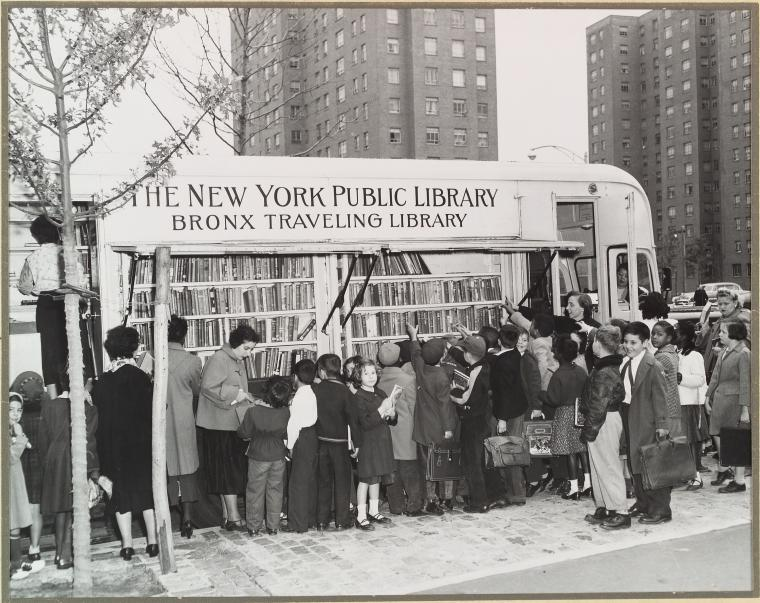 A crowd of children and their mothers gather around a van labeled New York Public Library, Bronx Travelling Library