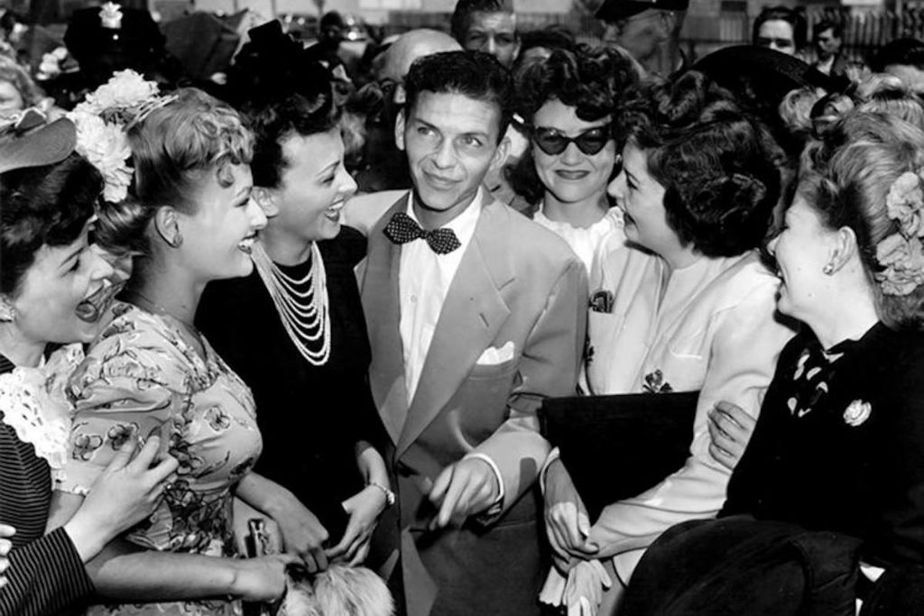 Young Frank Sinatra surrounded by beautiful smiling women.