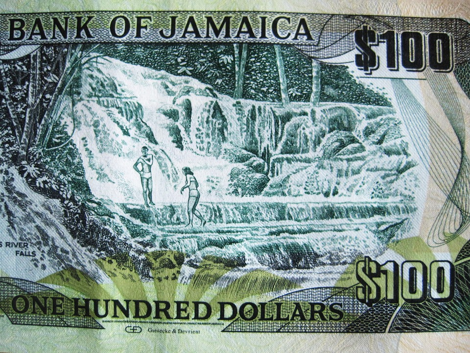 Green $100 dollar bill from Jamaica showing a man and a woman in swimsuits walking across the bottom of a waterfall.